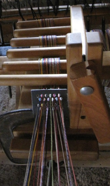 From the warping stand, the threads go through a tension box.