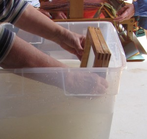 Paper making frame is pulled through a tub of water that contains pulp.